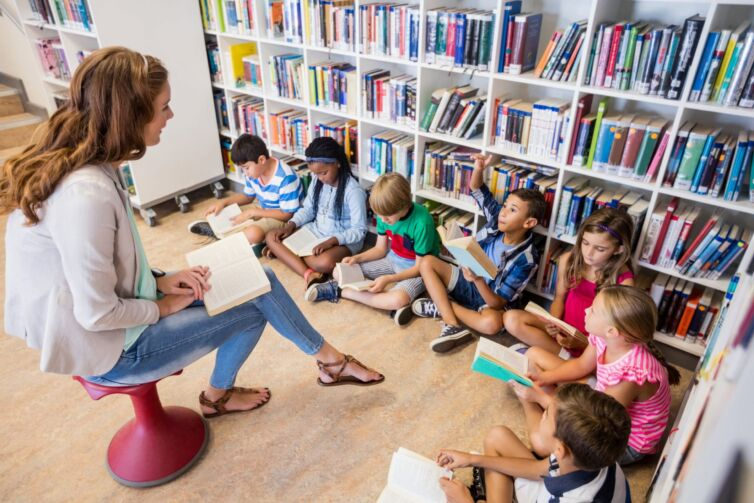 primary-school-teacher-in-libary-with-pupils-reading-scaled